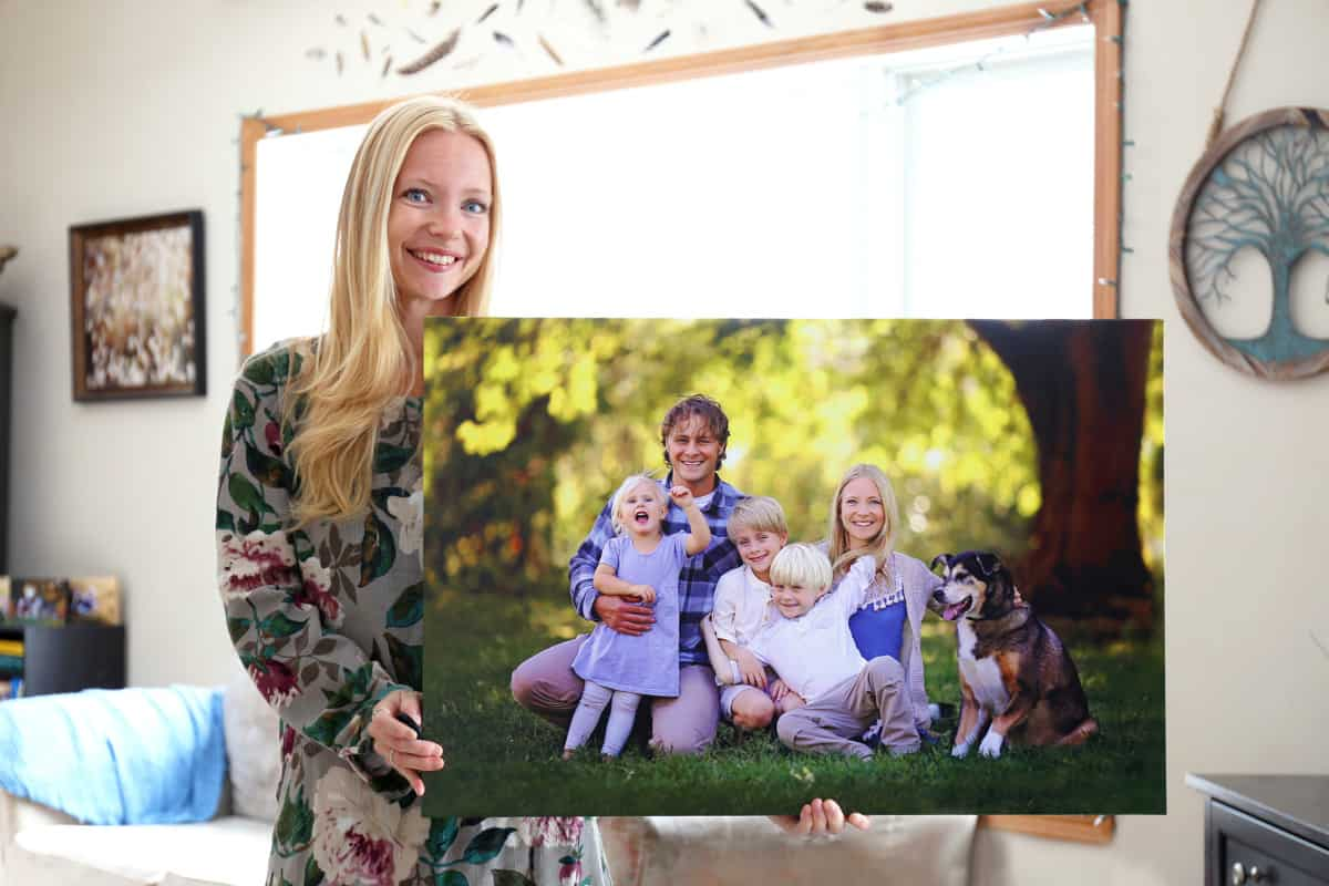 Happy Young Woman Holding Canvas Print of Family Portrait